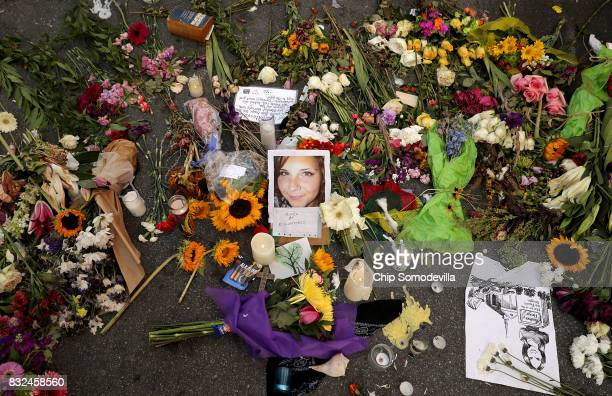 Flowers candles and chalkwritten messages surround a photograph of Heather Heyer on the spot where she was killed and 19 others injured when a car...
