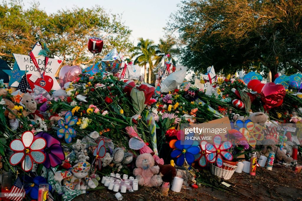 Flowers, candles and mementos sit outside one of the makeshift memorials at Marjory Stoneman Douglas High School in Parkland, Florida on February 27, 2018. Florida's Marjory Stoneman Douglas high school will reopen on February 28, 2018 two weeks after 17 people were killed in a shooting by former student, Nikolas Cruz, leaving 17 people dead and 15 injured on February 14, 2018. /