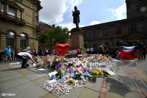 Flowers candles and other tributes in memory of the victims of the May 22 terror attack at the Manchester Arena are piled around the statue of...