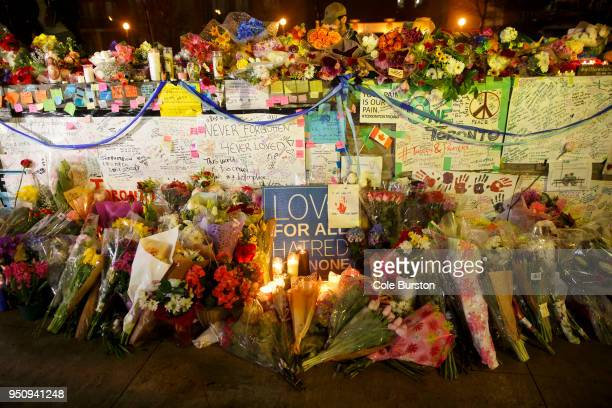 Flowers cards and words of sympathy adorn a makeshift memorial for victims of the mass killing on April 24 2018 in Toronto Canada A suspect...