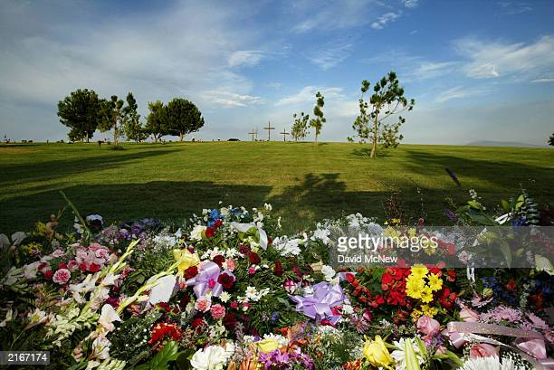 Flowers cover the gravesite of five family members who were found shot to death in their home last week July 16 2003 in Bakersfield California The...