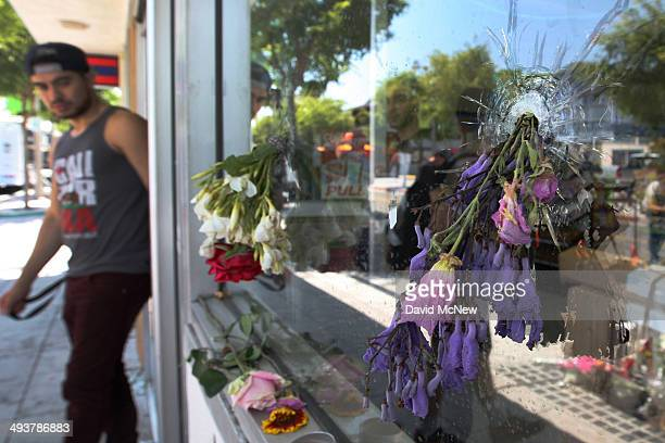 Flowers fill bullet holes in the windows of the IV Deli on May 25 2014 in Isla Vista California According to reports 22 year old Elliot Rodger son of...