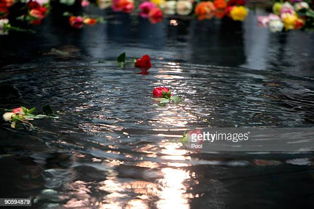Flowers float in the reflecting pool after family members of victims placed them as they gathered at Ground Zero during a 9/11 memorial ceremony on...