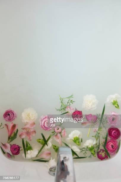 Flowers floating under faucet in a milk bath