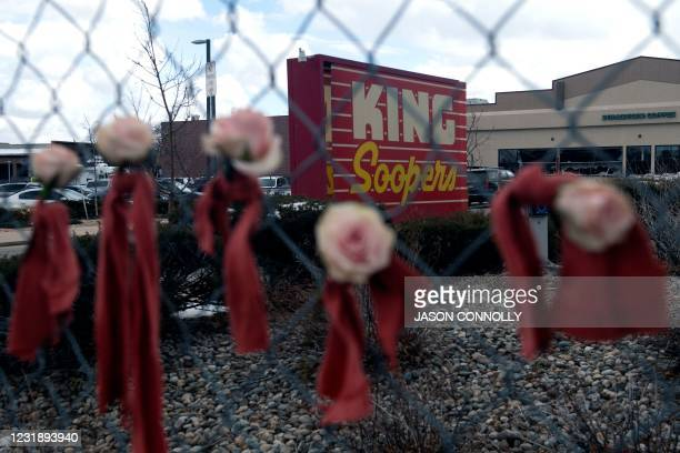 Flowers hang from the perimeter fence outside a King Soopers grocery store in Boulder, Colorado, on March 23 one day after a mass shooting left ten...