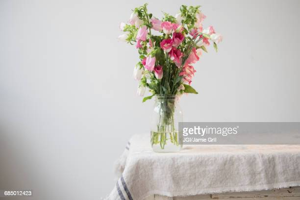 Flowers in jar of water at the edge of table