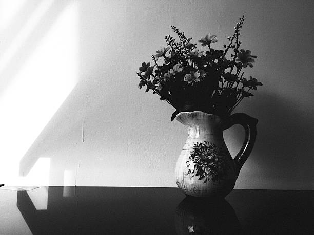 Flowers In Pitcher On Table At Home