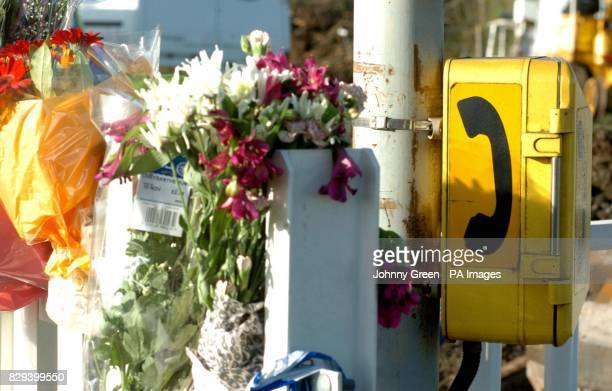 Flowers in tribute to the victims of the Berkshire train crash are placed next to the emergency telephone box used by the offduty policeman who...
