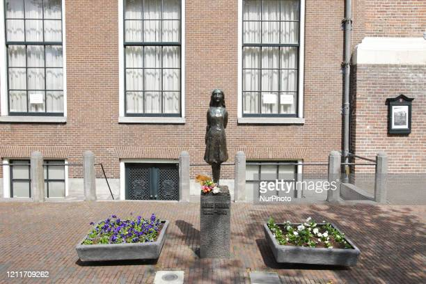 Flowers laid at the Anne Frank statue near Anne Frank house on empty street during the Remembrance Day to celebrate 75 Years of the War victims amid...