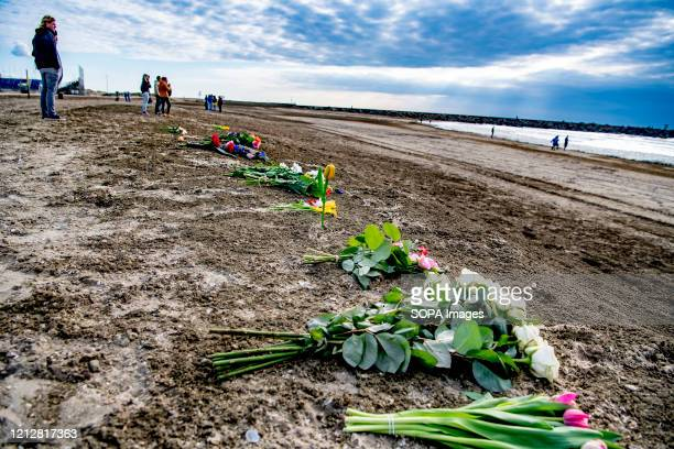 Flowers laid by friends and family on the beach during a commemoration to the deceased. The search for possibly three more missing surfers who were...