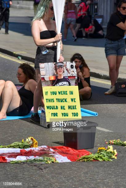 Flowers laid on the Canadian flag during the demonstration At the Canadian Embassy in London protesters demand Canada to stop Bill 156 that protects...