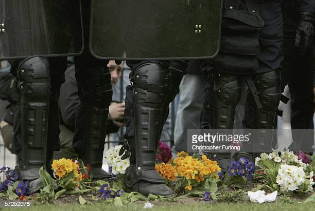 Flowers lay at the feet of riot police officers standing on Place d'Italie at the end of a rally against the youth employment contract known as CPE...