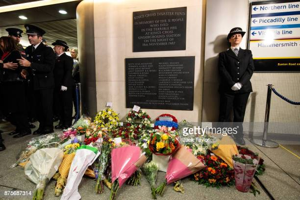 Flowers lay below a memorial plaque following a service to mark the 30th anniversary of the King's Cross fire at King's Cross Station on November 18...