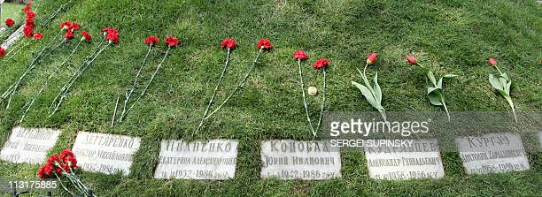 Flowers lay on the grass above plaques of dead Liquidators 21 April 2006 part of some 600000 front line soldiers firemen and civilians who were...
