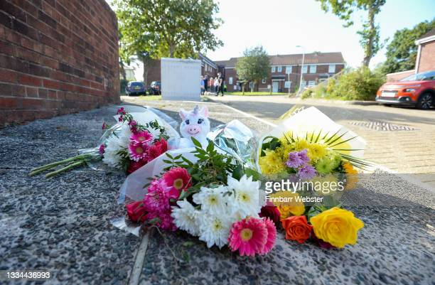 Flowers lay on the pavement of Biddick Drive on August 16, 2021 in Plymouth, England. Police were called to a multiple shooting in the Keyham area of...