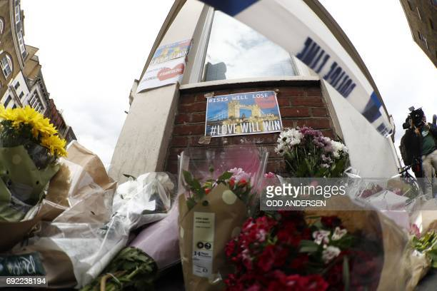 Flowers layed at a police cordon are seen on Borough High Street south of Borough Market below posters regarding the May 22 Manchester terror attack...