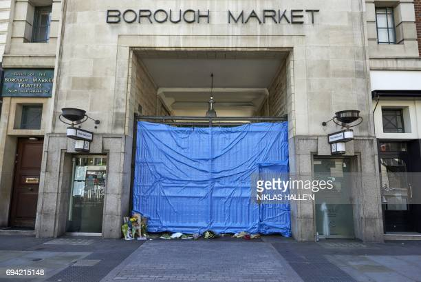 Flowers lie at a covered entrance to Borough market in London on June 9 following the June 3 terror attack that targeted members of the public on...
