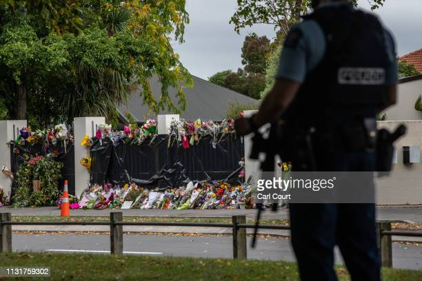 Flowers lie by the wall of Al Noor mosque as an armed policeman guards nearby on March 21 2019 in Christchurch New Zealand 50 people were killed and...