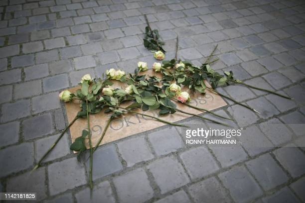 TOPSHOT Flowers lie on a memorial plate for the nonviolent protest march on October 9 1989 in Leipzig on May 8 2019