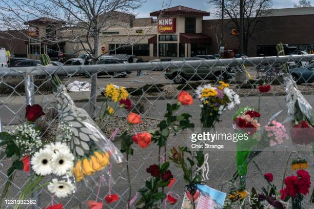 Flowers line a fence at a makeshift memorial for the victims of the shooting at a King Soopers grocery store on March 25, 2021 in Boulder, Colorado....