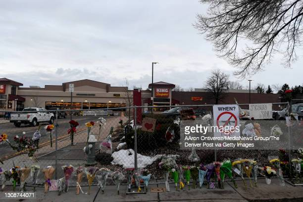 """Flowers line an ever-growing memorial along the sidewalk and fence a day after Monday""""u2019s mass shooting at King Soopers on Tuesday, March 23,..."""