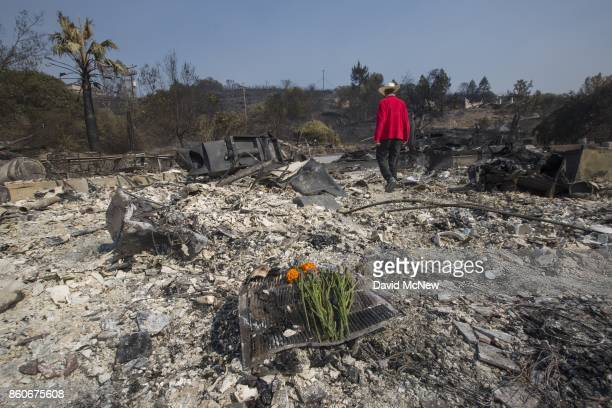 Flowers mark the spot where his father died as Mike Rippey walks through the ruins of the house of 100-year-old Charles and 98-year-old Sara Rippey,...