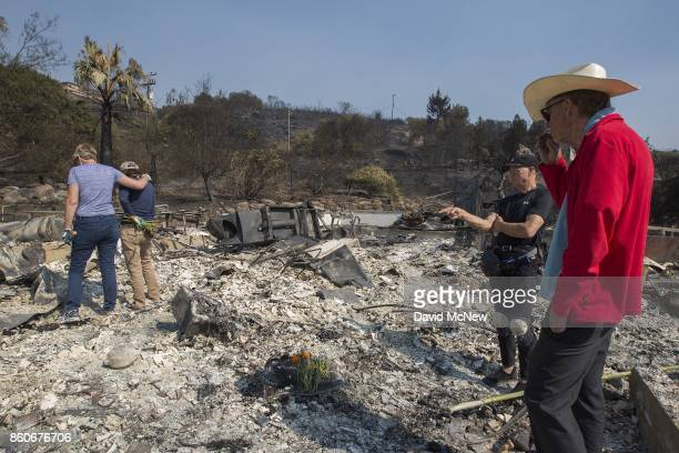 Flowers mark the spot where their father died as Rippey family daughters Liz and Mimi, and sons Chuck and Mike stand in the ruins of a house on...