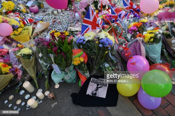 Flowers messages and candles are pictured alonside a tshirt from Ariana Grande's Dangerous Woman tour in St Ann's Square in Manchester northwest...
