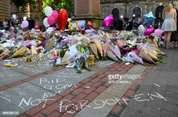 TOPSHOT Flowers messages and candles are pictured in St Ann's Square in Manchester northwest England on May 25 placed in tribute to the victims of...