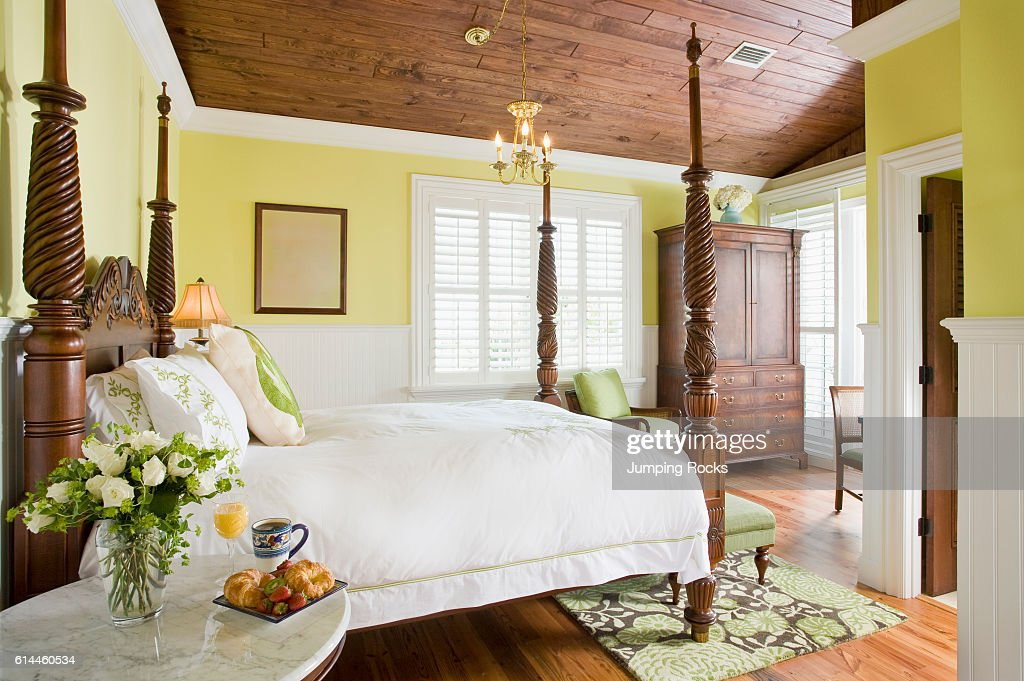 Flowers On Bedside Table Next To Wooden Four Poster Bed In Yellow News Photo Getty Images