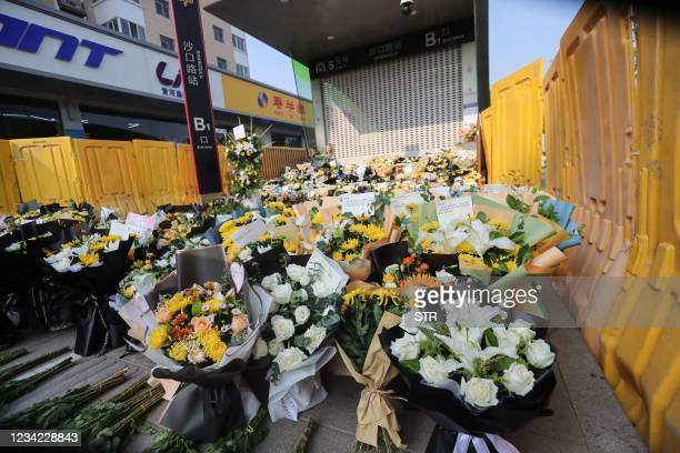 Flowers placed as tributes are seen in front of a subway station in memory of flood victims in Zhengzhou, China's central Henan province on July 27,...