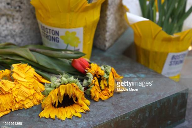 Flowers placed at the memorial to the victims of the Boston Marathon bombings near the Boston Marathon finish line on April 20 2020 in Boston...