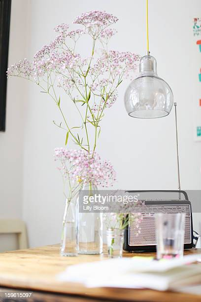 Flowers, radio and water glass on table