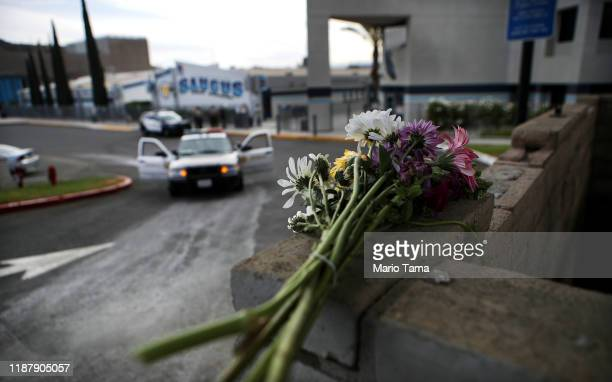 Flowers rest on a wall as police cars are parked at Saugus High School the day after a deadly shooting there on November 15 2019 in Santa Clarita...