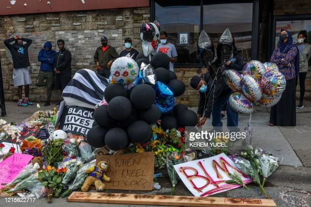 Flowers signs and balloons are left near a makeshift memorial to George Floyd near the spot where he died while in custody of the Minneapolis police...