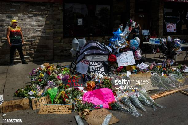 TOPSHOT Flowers signs and balloons are left near a makeshift memorial to George Floyd near the spot where he died while in custody of the Minneapolis...
