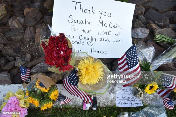 Flowers signs and photos are seen at a makeshift memorial to US Senator John McCain in Phoenix Arizona August 26 2018 McCain who died on August 25 at...