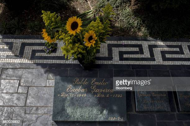 Flowers sit at the grave site of narcotics kingpin Pablo Escobar at the Montesacro Cemetery in Medellin, Colombia, on Tuesday, Oct. 3, 2017. In...
