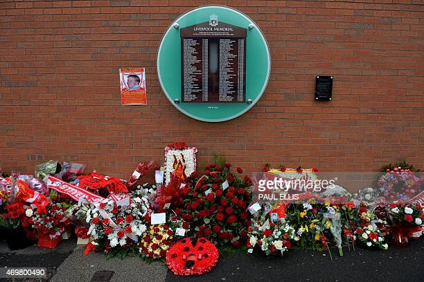 Flowers sit beneath the temporary Hillsborough memorial ahead of a memorial service at Anfield in Liverpool north west Engand on April 15 on the 26th...