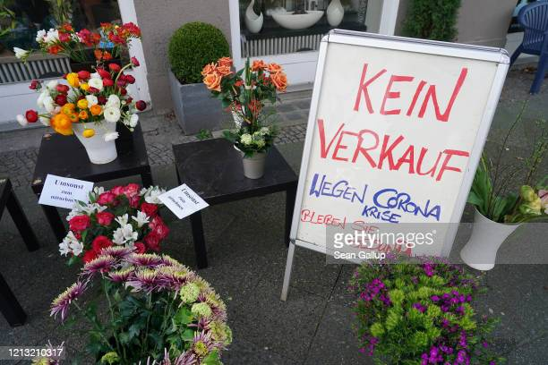 Flowers stand on display and being given away for a free at a florist's closed following a city ordinance temporarily closing all non-essential shops...