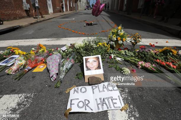 Flowers surround a photo of 32-year-old Heather Heyer, who was killed when a car plowed into a crowd of people protesting against the white...