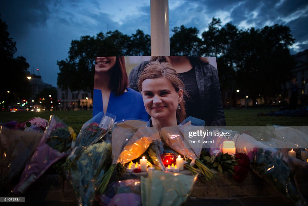 Flowers surround a picture of Jo Cox during a vigil in Parliament Square on June 16, 2016 in London, United Kingdom. Jo Cox, 41, Labour MP for Batley and Spen, was shot and stabbed by an attacker at her constituicency today in Birstall, England. A man also suffered slight injuries during the attack. Jo Cox was reportedly shot and stabbed while holding her weekly surgery at Birstall Library, Birstall near Leeds and later died. A 52-year old man has been arrested in connection with the crime.
