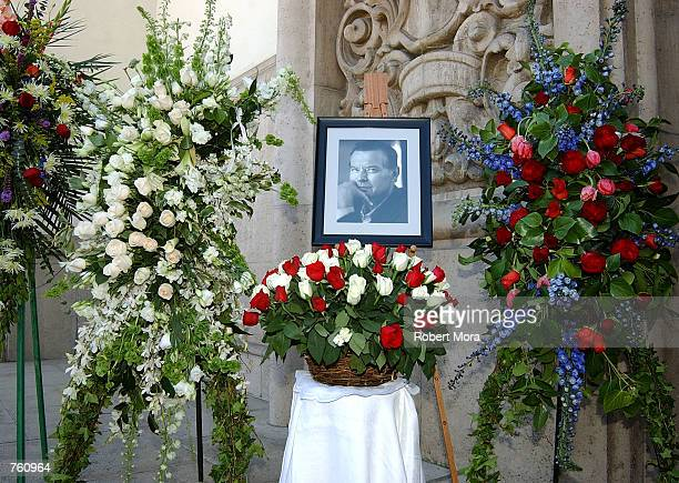 Flowers surround a portrait of late actor Robert Urich during the funeral service at Saint Charles Borromeo Catholic Church April 19 2002 in North...