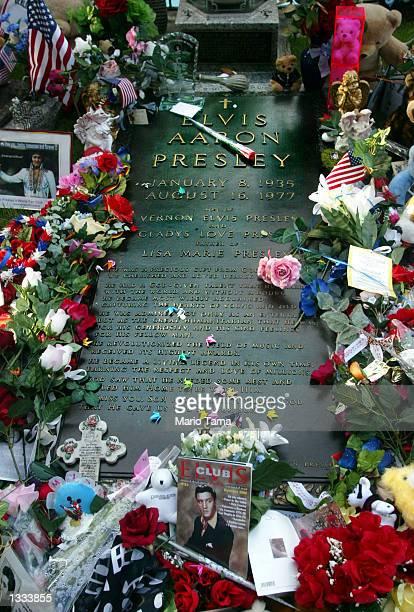 Flowers surround Elvis Presley's gravestone in the 'Meditation Gardens' area of Graceland during Elvis Week on August 12 2002 in Memphis Tennessee...