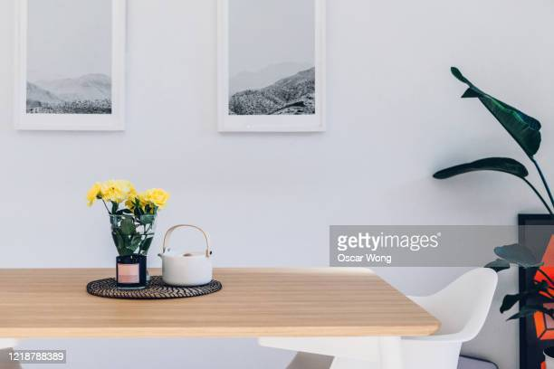 flowers, teapot and scented candle on the dining table - tidy room stock pictures, royalty-free photos & images