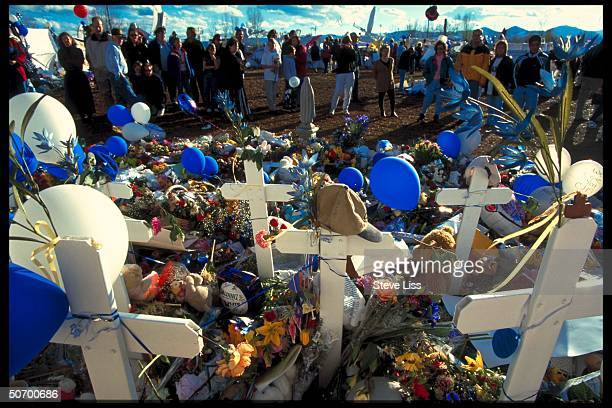 Flowers tokens lad at makeshift memorial in remembrance of 13 victims killed by troubled seniors Dylan Klebold Eric Harris who went on shooting spree...
