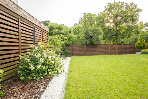 Flowers, trees and green grass in the garden of house with wooden screen. Real photo 1002780128