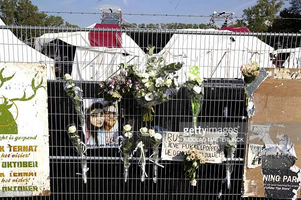 Flowers tucked into wire fencing frame a photograph of Wendy and Marlo victims of last night's tent collapse during the Pukkelpop music festival in...