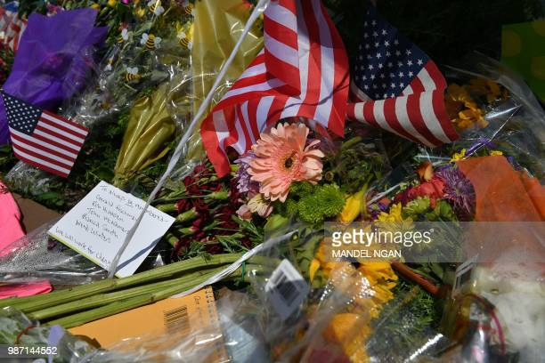Flowers US flags and messages adorn on June 29 a makeshift memorial for five people killed at the Capital Gazette newspaper on June 28 in Annapolis...