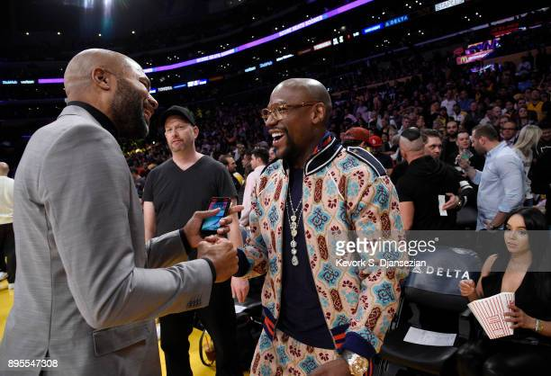 Floyd Joy Mayweather Jr speaks with former Los Angeles Lakers player Derek Fisher as they attend a basketball game between the Golden State Warriors...